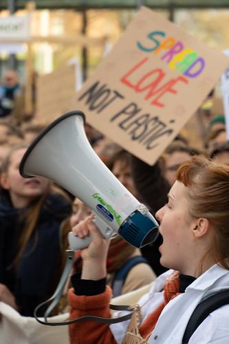 Demonstrant*innen mit Megafon und Schild mit Aufschrift: spread love, not plastic.