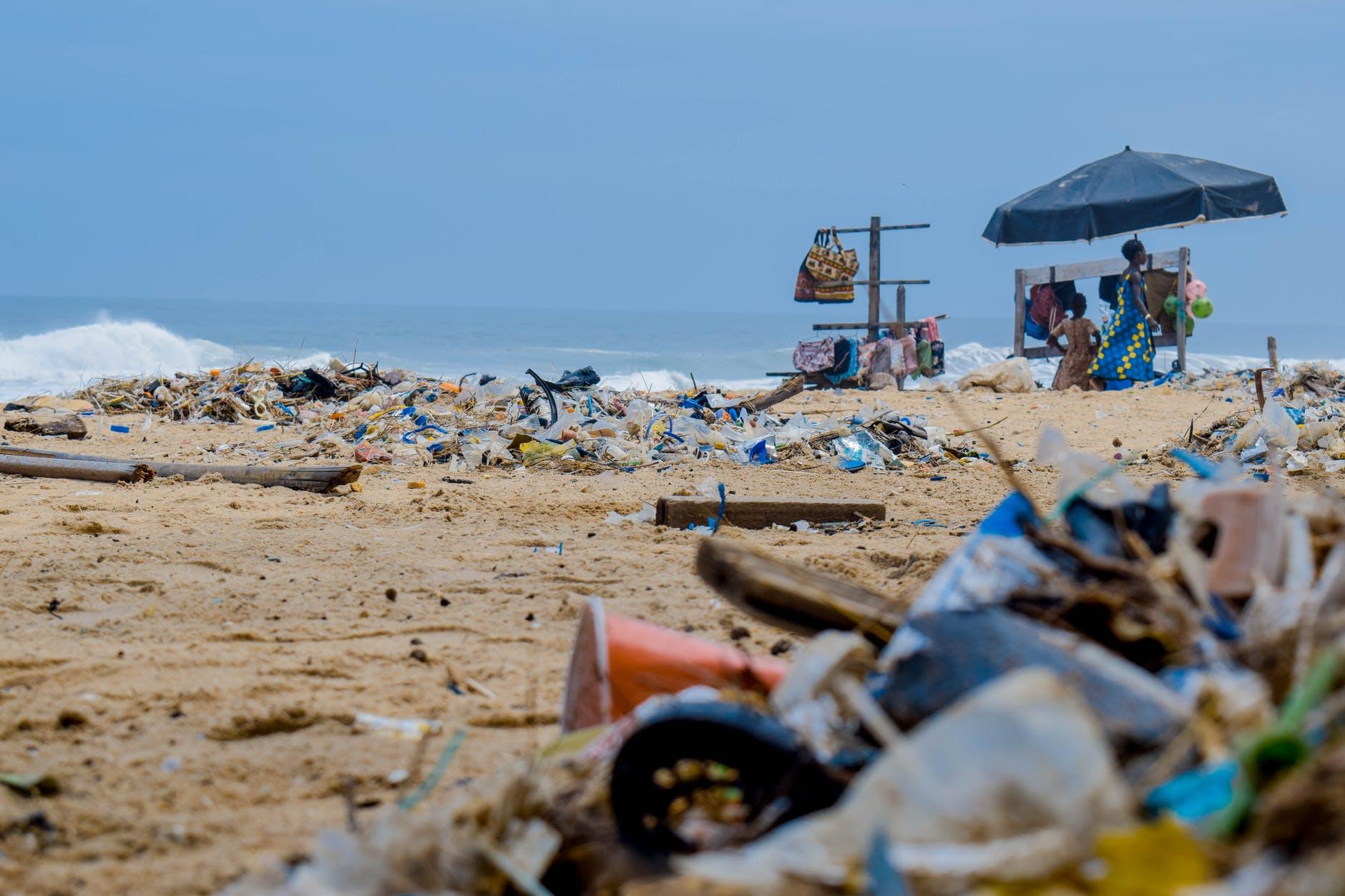 Ein Strand voller Plastikmüll mit zwei afrikanischen Frauen im Hintergrund.