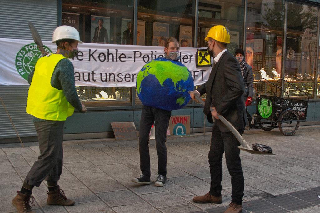 Klimastreik vor der Raiffeisenbank. Sketch: Eine Pappmaché-Erde läuft besorgt neben Kohle-Arbeiter*innen umher.