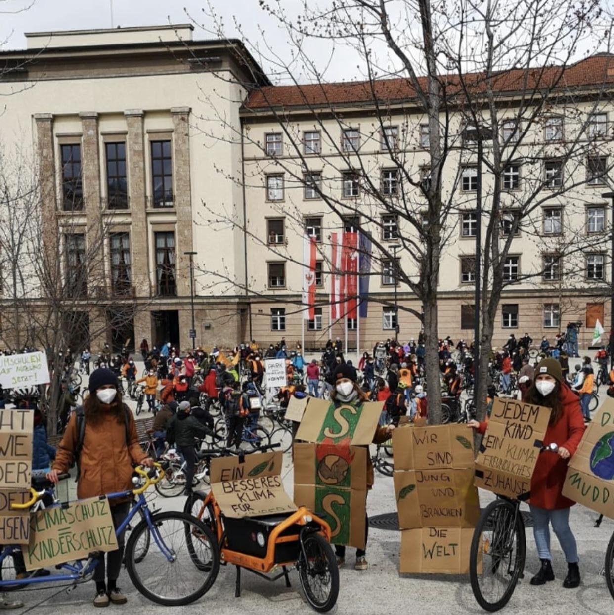 Menschen mit Lastenrad und Streikschildern stehen im Vordergrund vor einer Klima-Demonstration in Innsbruck