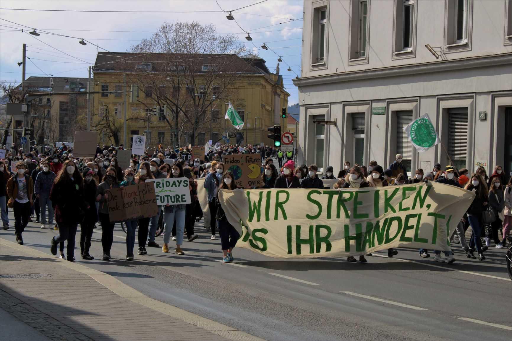 Junge Menschen in einem großen Demonstrationszug durch die Grazer Innenstadt mit Streikschildern und Frontbanner: Wir streiken bis ihr handelt