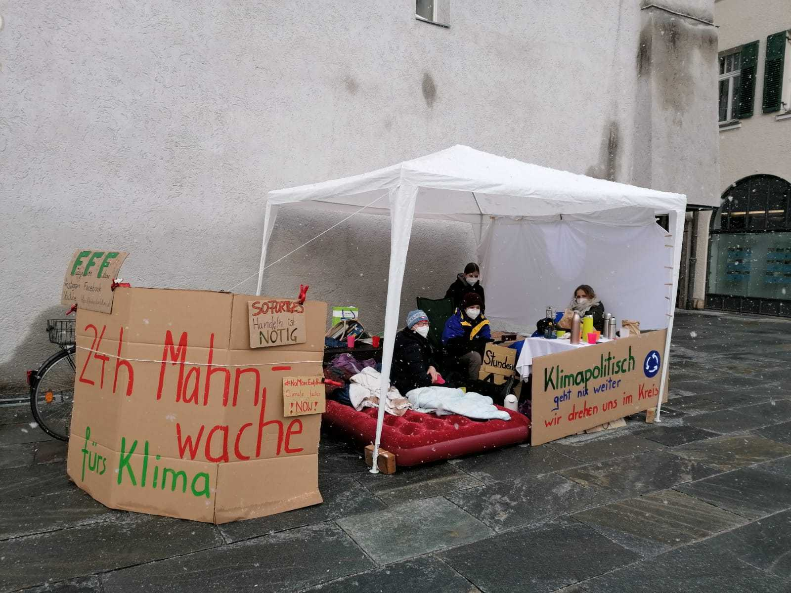 Menschen sitzen unter einem weißen Zelt auf Matratzen und protestieren 24 Stunden für Klimaschutz vor dem Kufsteiner Rathaus