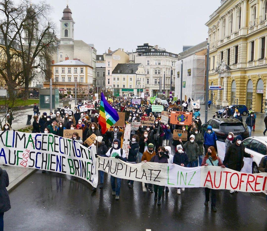 Großer Demonstrationszug durch die Linzer Innenstadt mit Frontbannern die Klimagerchtigkeit und einen autofreien Hauptplatz fordern