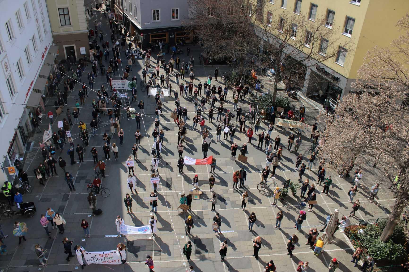 Menschen stehen gleichmäßig auf einem Platz verteilt mit Abstand und Schildern beim weltweiten Klimastreik in Graz