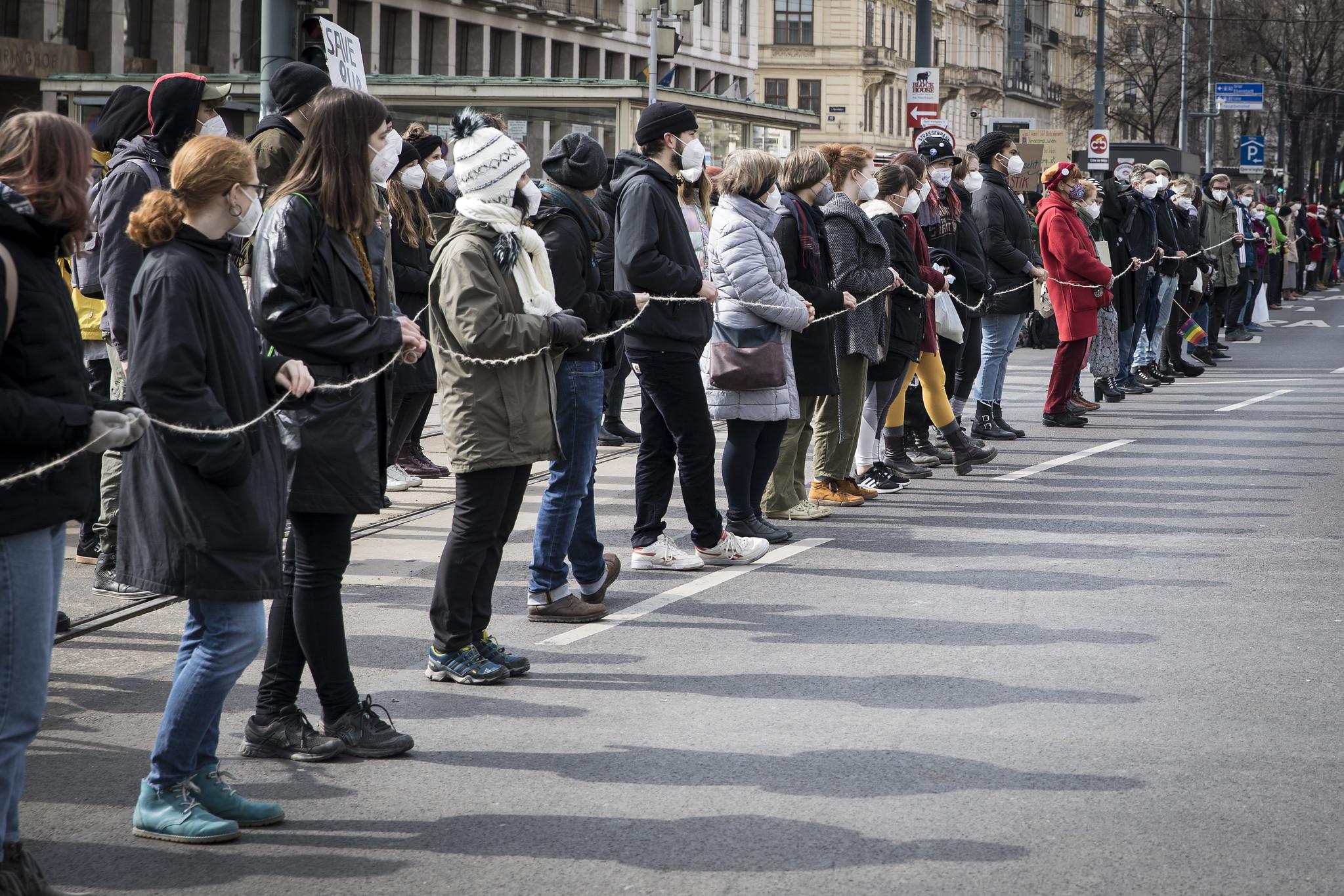 Personen stehen in langer Menschenkette auf der autofreien Wiener Ringstraße mit Abstand und verbunden über eine Schnur