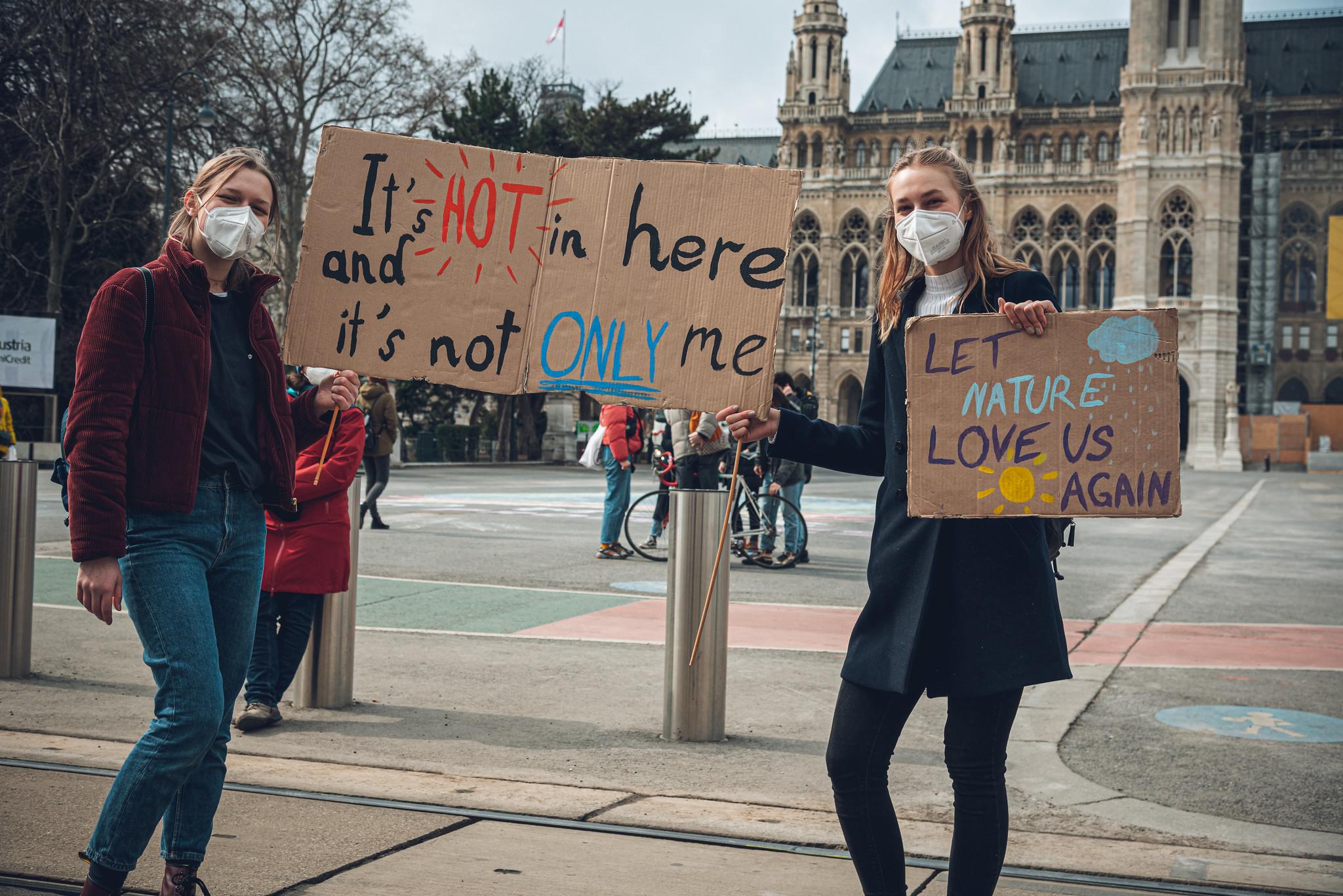 Zwei junge Frauen heben Streikschilder mit Klima-Sprüchen in die Höhe und stehen dabei auf der autofreien Ringfahrbahn in Wien
