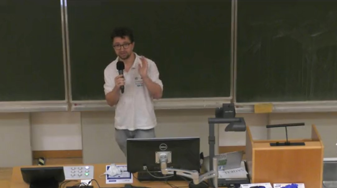 Screenshot der Vorlesung. Adrian steht mit Mikro vor der Tafel und erklärt etwas.