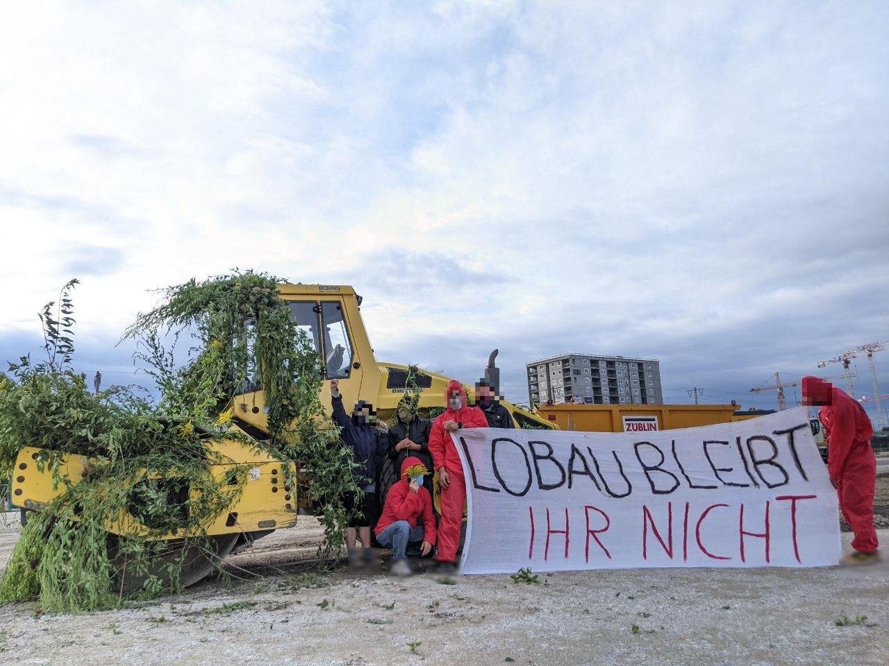 """Aktivistis stehen vor begrüntem Bagger mit Banner auf dem """"Lobau bleibt - ihr nicht"""" steht"""