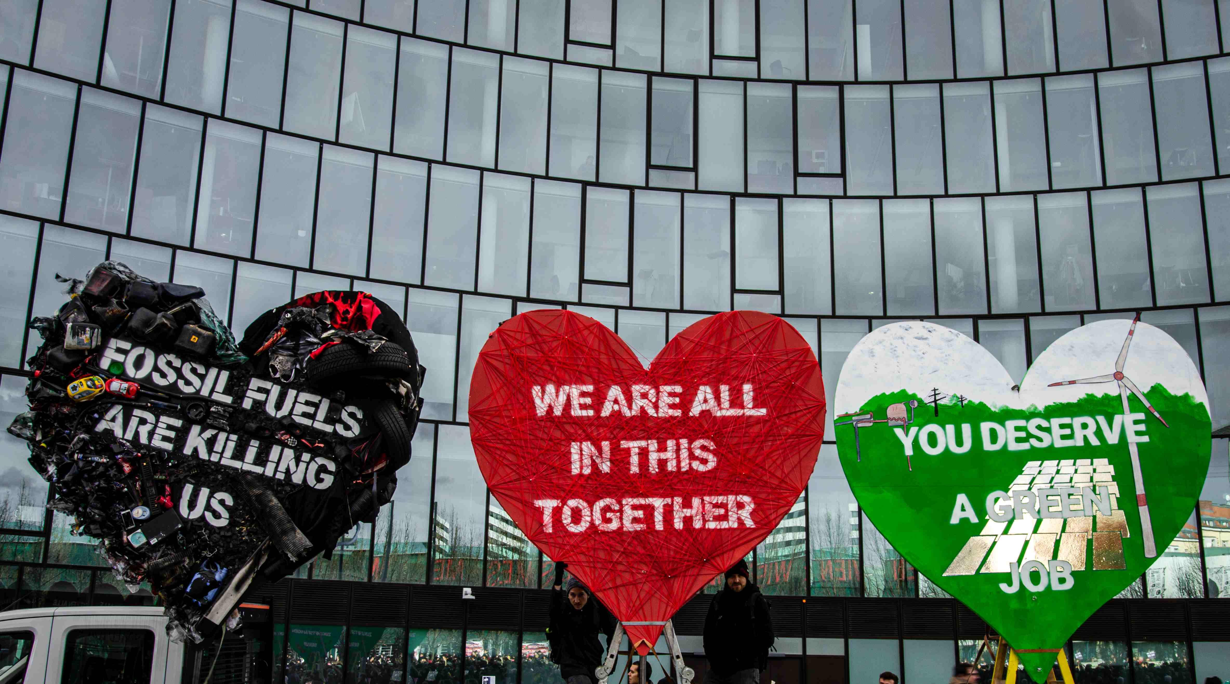 Drei gigantische, kreativ gestaltete Herzen mit Botschaften an die OMV stehen vor der OMV-Zentrale in Wien